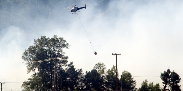 A helicopter helps to put out the blaze.  Photo/Ben Fraser