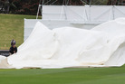 Groundsmen struggle to control the covers in gale winds after rain stops play. Photo / Mark Mitchell