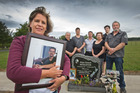 Judy Richards pictured holding a photograph of her son Rhys Middleton while other family members gather around the headstone at his graveside in Tauranga. Photo / Alan Gibson