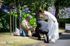 Bronia Tindall and Fabrizio Clementi share a slice of their wedding cake with Miller outside The Community of St Luke Church in Remuera. Photo by Ben Franks/Steve May/one2one Photography