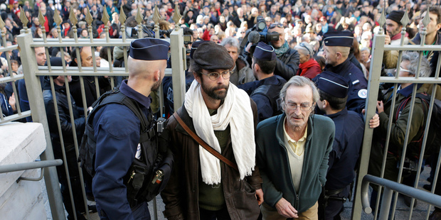 Cedric Herrou, center, a French activist farmer who faces up to five years in prison as he goes on trial accused of helping African migrants cross the border from Italy. Photo / AP