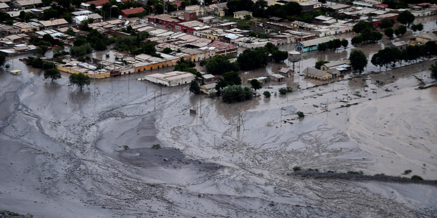 Flooded roads are covered in mud. Photo / AP