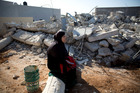An Israeli Arab woman sits by the rubble of demolished house in Kalansua, Israel. Photo / AP