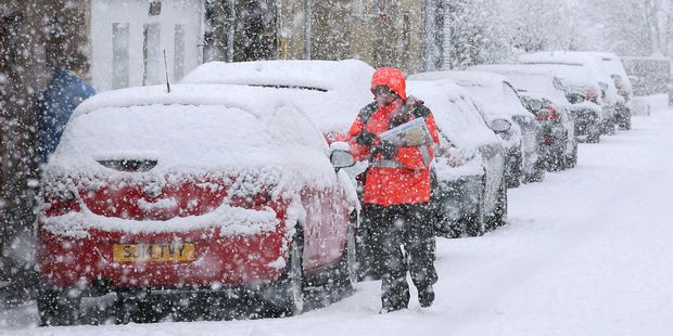 Loading A postman struggles in the snow while making deliveries in Stirling, Scotland. Photo / AP