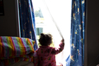 A 2-year-old girl looks out from the one-room rental shared by her mother and father at an accommodation lodge in Mangere, Auckland. New Zealand Herald Photograph by Richard Robinson.