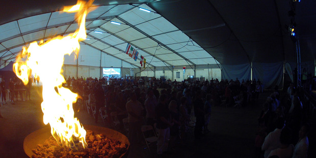 The games torch burns brightly in the village main tent in 2015. The village moves out of the tent to the War Memorial Hall this year.