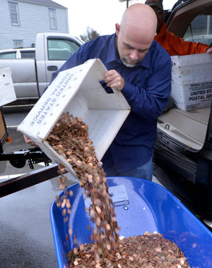 Nick Stafford fills one of five wheelbarrows full of change, mostly pennies. Photo / AP