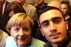 German Chancellor Angela Merkel poses with Anas Modamani for a selfie.