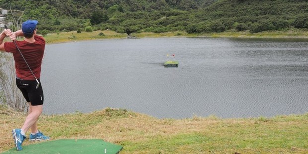 A punter tries his luck on the Westland floating golf course. Photo / Hokitika Guardian