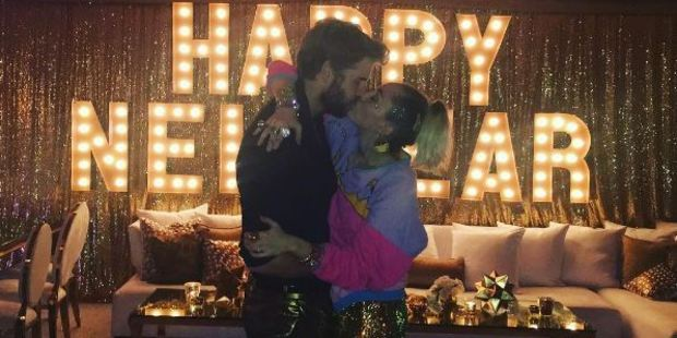Miley Cyrus and Liam Hemsworth may have been celebrating more than the New Year as they marked 2017 with a passionate kiss. Photo / Miley Cyrus Instagram