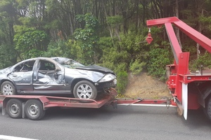 The car which plunged down a bush-clad cliff on SH25a yesterday is towed from the scene this morning. Photo / Hunter Calder/Herald Local Focus