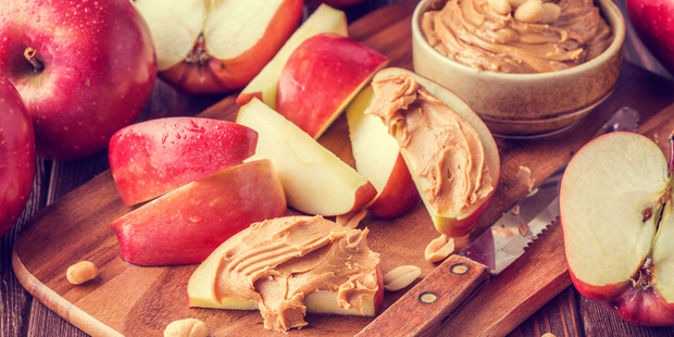 Try peanut butter on apple for a delicious and nutritious snack. Photo / Getty Images