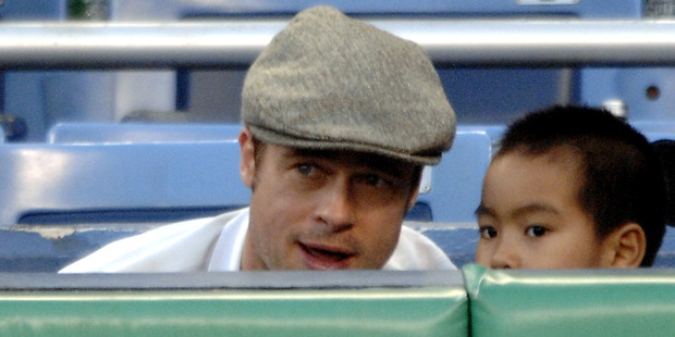 Brad Pitt discusses some of the finer points of baseball with his son Maddox. Photo / Getty