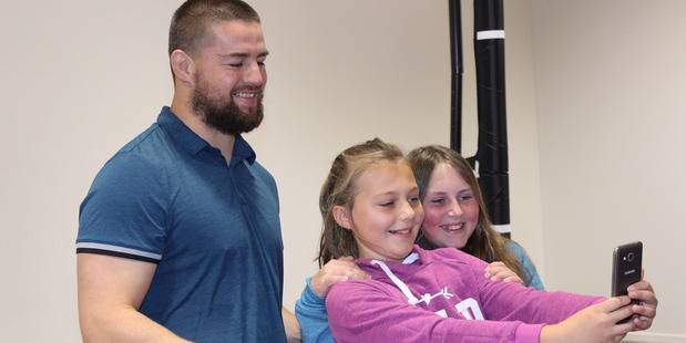 SMILE: Te Horo School pupils Lily Forsyth, pink top, and Lana Whitton, blue top, take a selfie with Dane Coles.