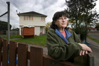 Shirley Butler in front of some of the boarded-up state houses on Jebson Place in Hamilton today. Photo / Alan Gibson