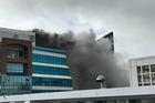 The massive fire at the corner of Mayoral Drive and Queen St in central Auckland sent plumes of black smoke billowing into the Auckland skyline yesterday. Photo / Supplied