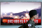 A South Korean army soldier walks by a TV news programme showing a file image of missiles being test-launched by North Korea. Photo / AP