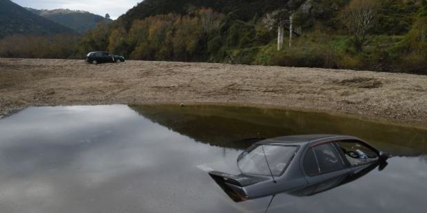 A Nissan Primera sits on the bed of the Taieri River, and a Nissan Sentra lies abandoned at Outram Glen on Wednesday. Photo / Otago Daily Times
