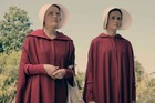 Elisabeth Moss,left, is draped in a red cloak in a scene from The Handmaid's Tale.