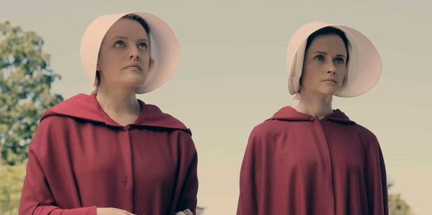 Loading Elisabeth Moss,left, is draped in a red cloak in a scene from The Handmaid's Tale.