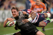 Jed Brown of the Crusaders is tackled by Marika Koroibete of the Rebels. Photo / AAP