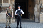 An armed soldier and policeman stand guard at Parliament. Photo / AP