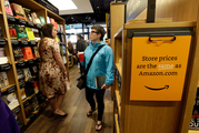 Customers browse aisles Amazon Books, the first brick-and-mortar retail store for online retail giant Amazon, in Seattle. Photo / AP