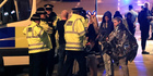 Emergency services personnel speak to people outside Manchester Arena. Photo / AP