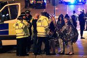 Emergency services personnel speak to people outside Manchester Arena after reports of an explosion at the venue during an Ariana Grande concert in Manchester. Photo / AP
