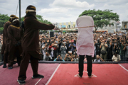 Shariah law official whips one of two men convicted of gay sex during a public caning outside a mosque in Banda Aceh, Aceh province Indonesia. Photo / AP