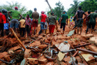 Sri Lankan military rescuers and villagers stand on the debris of a house that was destroyed in a landslide in Bellana village in Kalutara district, Sri Lanka. Photo / AP
