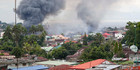 Fires rage at several houses following airstrikes by Philippine Air Force in Marawi city. Photo / AP