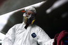 A member of Enviro decontaminates a window inside a Napier property used as a P Lab. Photo / Paul Taylor