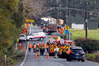Emergency services workers and Fulton Hogan colleagues at the scene on Otaika Valley Rd where a man was killed. Photo/John Stone