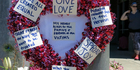 A heart-shaped wreath covered with positive messages hangs on a traffic light pole at a memorial for two bystanders who were stabbed to death. Photo / AP