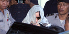 Australian drug smuggler Schapelle Corby covered her head with a scarf gets on a car as she leaves the parole office in Bali. Photo / AP