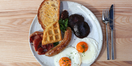The glazed free-range bacon, house kransky, fried eggs, field mushrooms and waffle hash. Photo / Getty Images