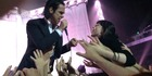 Nick Cave serenades an audience member during his Vector Arena concert in Auckland. Photo credit: Jonathan Maze.