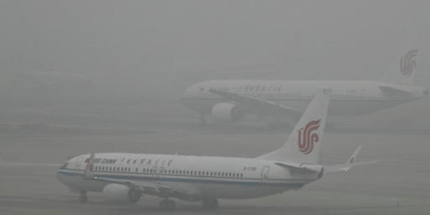 Air China passenger planes preparing to take off at the Beijing Capital International Airport while shrouded by heavy smog. Photo / AP