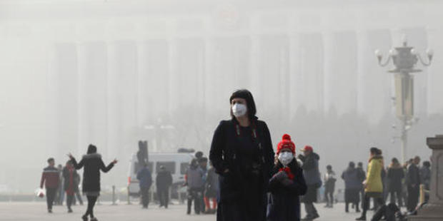 A tourist and a child wearing protection masks walk through Tiananmen Square in Beijing as the capital of China is blanked by heavy smog. Photo / AP