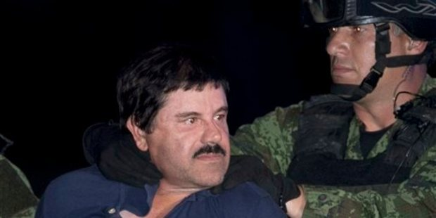Joaquin 'El Chapo' Guzman is made to face the press as he is escorted to a helicopter in handcuffs by Mexican soldiers and marines. Photo / AP