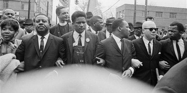 Dr Martin Luther King, Jr. locks arms with his aides as he leads a march in Montgomery, Alabama, March 17, 1965. From left: Ralph Abernathy, James Foreman, King, Jesse Douglas, Sr., and John Lewis.
