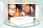 Young man and woman looking at microwave meal in microwave