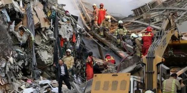 Firefighters work during the operations removing debris from the collapsed building. Photo / AP