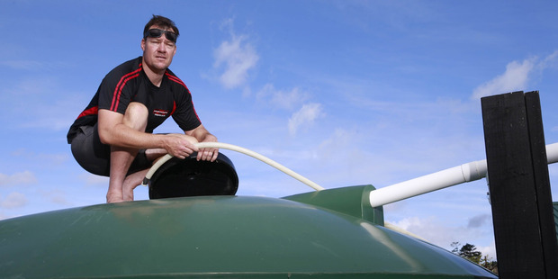 Loading Mangawhai resident Brett Calhoun does what he can to fill his and his family's 25,000L water tank. Photo / Nick Reed