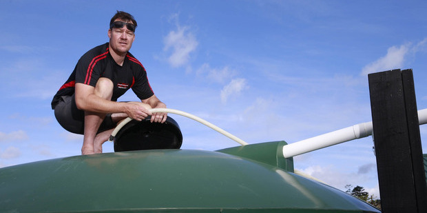 Loading Mangawhai resident Brett Calhoun does what he can to fill his and his family's 25,000L water tank Photo / Nick Reed