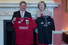 Bill English tries some rugby diplomacy with British Prime Minister Theresa May, who holds an All Black jersey while he displays a Lions one. Photo / Supplied