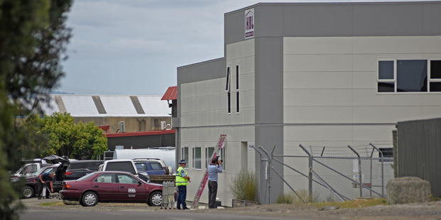 Police examine bullet holes in the side of the HBL Builders premises. Photo / George Novak.
