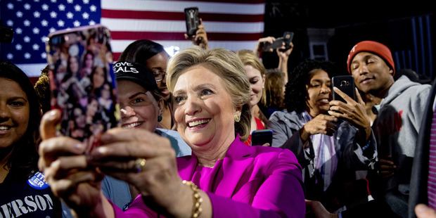 Hillary Clinton takes a selfie with supporters. Photo / AP