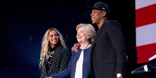 Hillary Clinton, center, appears on stage with artists Jay Z and Beyonce. Photo / AP